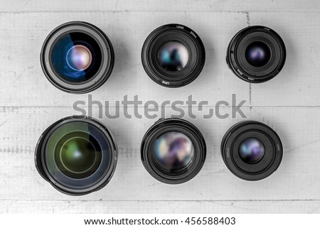 camera lenses laying on white wooden background