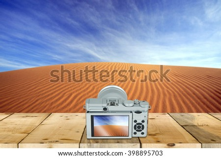 camera with screen display on wooden table with beautiful landscape in the background