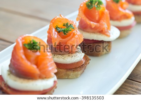 canapes with salmon and cheese on wooden table