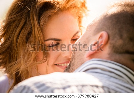 Candid close up photo of man kissing young smiling woman