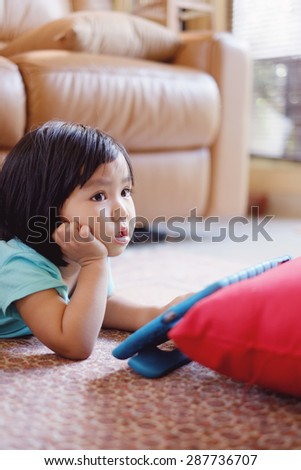 Candid picture of baby girl watching television while holding tablet
