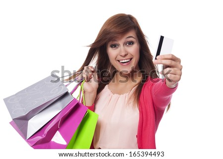 Candid young woman showing credit card and holding shopping bags
