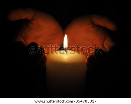candle and hands on a black background
