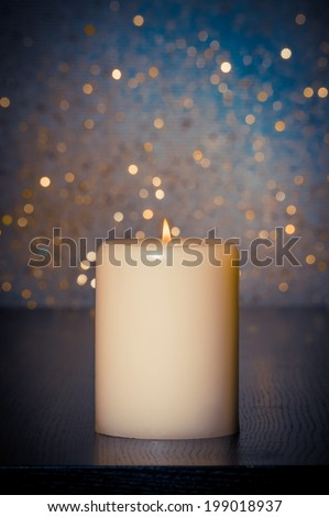 candle with flame on wood table and blue bokeh background and space for text