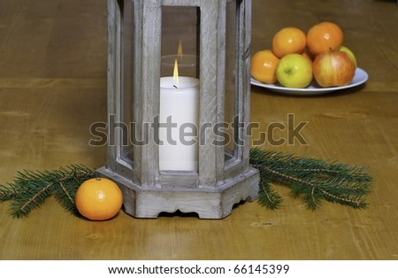 Candle with some fruits and dekos on a table