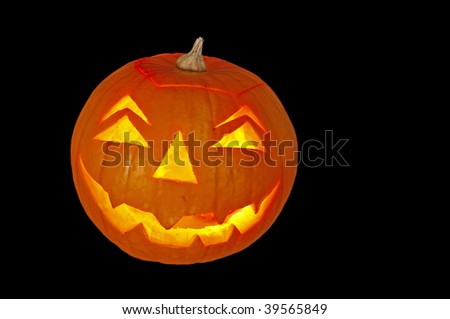 candlelit glowing pumpkin lantern isolated on black