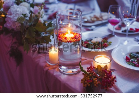 Candles and flowers on a table in the evening.