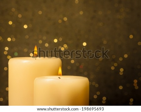 candles with flame on golden bokeh background and space for text