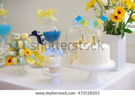 Candy bar decorated with sweets, cupcakes and cake for 1st birthday party
