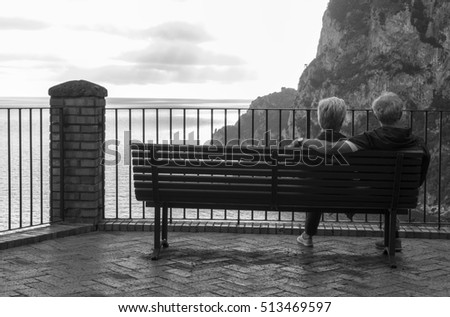 Capri, Italy - October 2, 2016: Black and white photograph of an elderly couple sitting on a park bench, his arm over her shoulders, waiting for a sunset over the Mediterranean Sea.