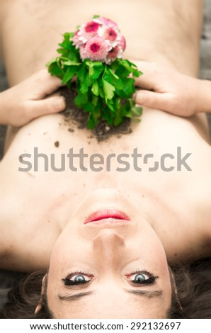Caption of nude woman from above angle with flower covering breasts