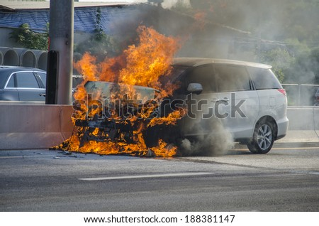 Car bursts into flames on a busy street.