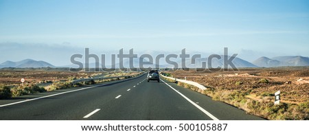 car driving away on road to mountains in Canary Island desert, Lanzarote, Spain, panorama