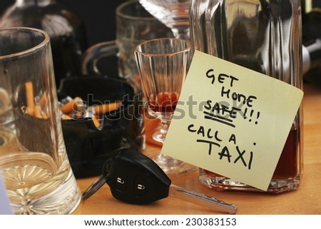 Car keys on the table full of empty glasses, bottles and ashtray at party, don't drink and drive concept, post it note for taxi