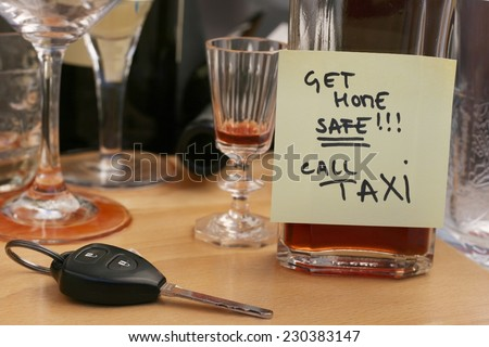 Car keys on the table full of empty glasses, bottles at party, don't drink and drive concept, post it note for taxi