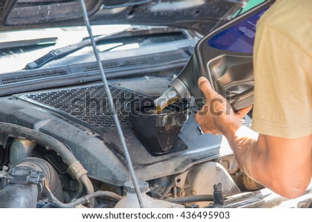 Car maintenance servicing mechanic pouring new oil lubricant into the car engine, A mechanic pours fresh oil into a car engine as part of its maintenance.