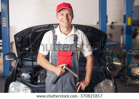 Car mechanic working on an engine at the repair shop