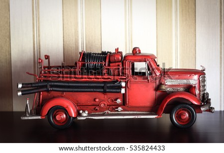 Car plastic model of an old classic red Fire Truck on a stripped wallpaper