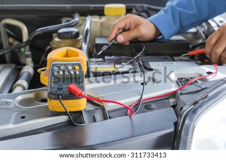 Car repair service, Auto mechanic checking a car battery level by voltmeter