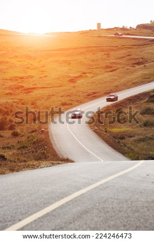 car running on  cranked road in grassland