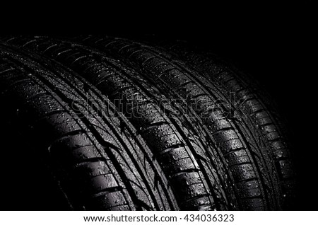 Car wet tyres on a black background.