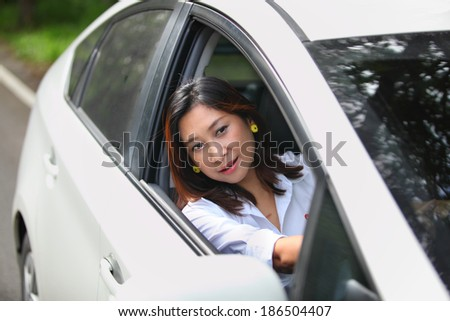 Car woman happy in new car. Young woman driving on road trip on beautiful sunny summer day. Pretty mixed race Asian / Caucasian female model.