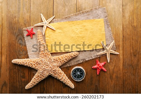 Card blank with sea stars and compass on wooden background