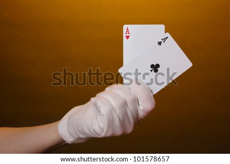 Cards in hand on brown background
