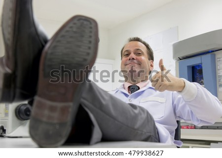 Carefree doctor in a laboratory has his feet on the desk. Scientist resting in the lab with thumbs up gesture. Successful research. Relax in the hospital.Lazy doc resting in office with legs on table.