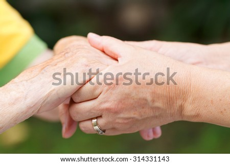 Caregiver touching and holds an elderly wrinkled hand