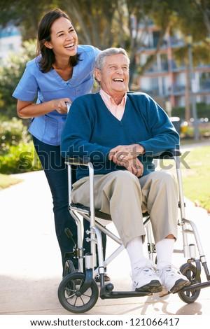 Smiling carer pushing an old man in a wheelchair stock photo image - Carer Pushing Senior Man In Wheelchair Stock Photo