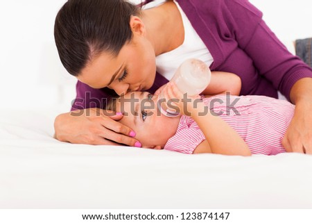 caring mother kissing baby daughter while she drinking milk