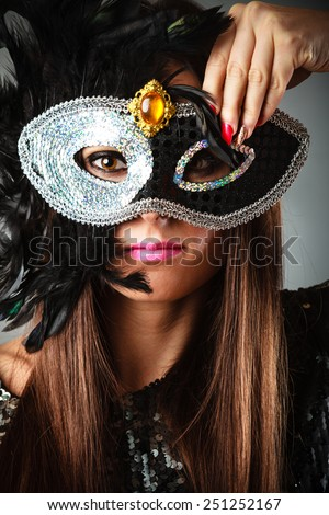 Carnival night life. Attractive woman face with hand holding mysterious mask on grey background in studio.