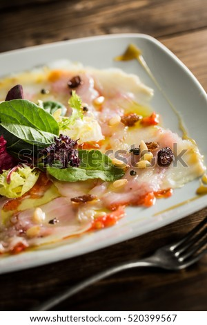 Carpaccio cod salad on a wood table.