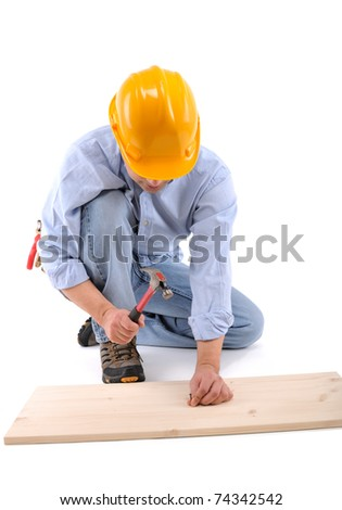 Carpenter nailing the wall with hammer isolated on white - a series of CONSTRUCTION IMAGES.