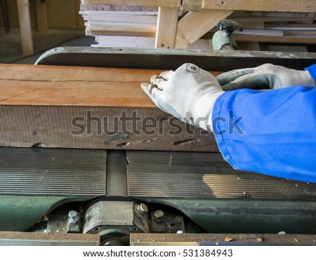 Carpenter workplace. Man using saw to cut wood.