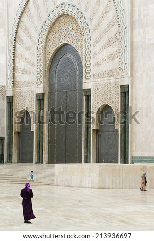 CASABLANCA, MOROCCO - JULY 23: Local people walking at a gate of King Hassan II Mosque on July 23, 2014 in Casablanca, Morocco. It is the largest Mosque in the country