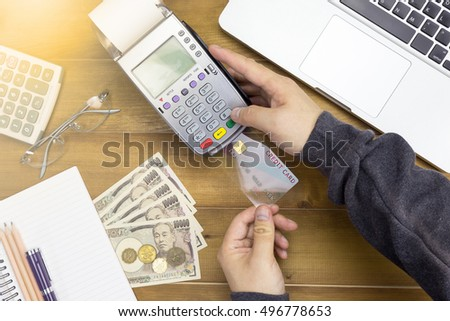 Cashier hand holding a Credit card over Japanese bank notes and EDC machine or credit card terminal with calculator and glasses. This is fake credit card.