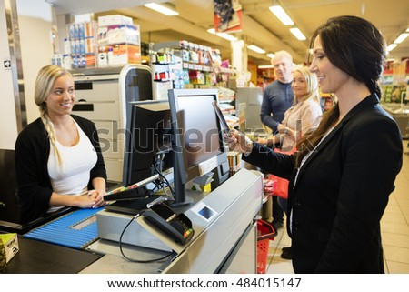 Cashier Looking At Female Customer Making Payment