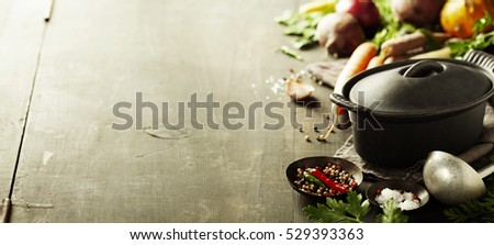 Cast iron pot and vegetables on wooden rustic table. Homemade food, cooking, vegetarian concept