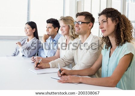 Casual business team listening during meeting in the office