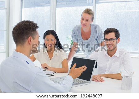Casual businessman using laptop during meeting in the office