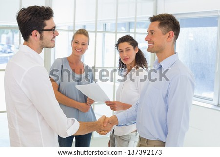 Casual businessmen shaking hands and smiling in the office