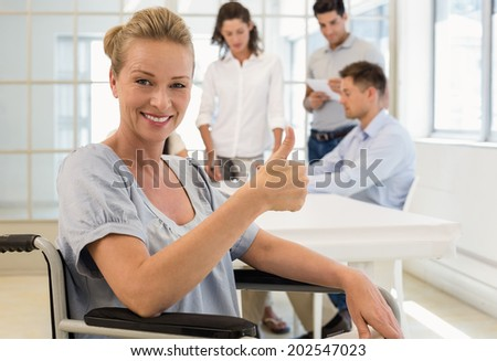Casual businesswoman in wheelchair smiling at camera with team behind her in the office