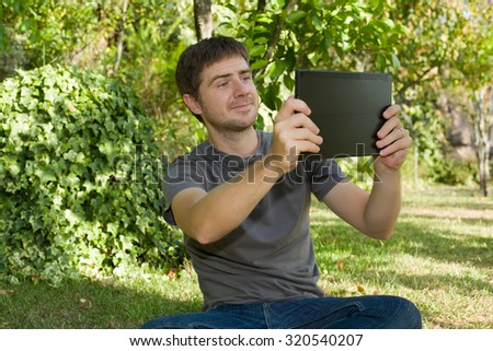 casual man taking a picture with a tablet pc, outdoor