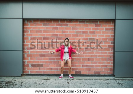 Casual young woman in front of a brick wall in the street