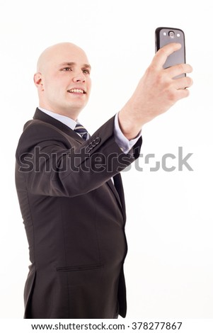 Caucasian businessman using smartphone to take picture of himself
