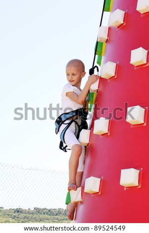 caucasian child undergoin treatment for cancer climbing a blow up castle at a fun fair