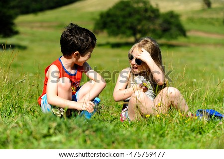 Caucasian Cute little boy and girl sitting on green grass in forest field