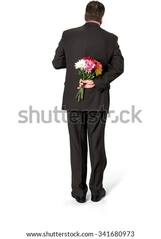 Caucasian elderly man with short medium brown hair in business formal outfit holding flowers - Isolated